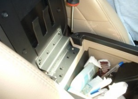 Remove screws securing center console lid with a screwdriver