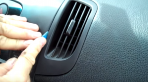 Pry the right air conditioner vent with a lever, and then remove it