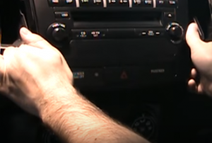 Release the radio cover panel and unplug the connector behind