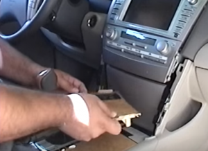 Pull out the panel near the shift lever and unplug the connector behind