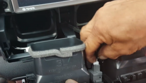 Disconnect the connector at the back of the air vent