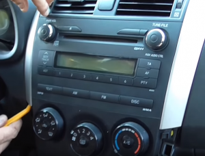 Remove the trim pieces above cup holder with a lever